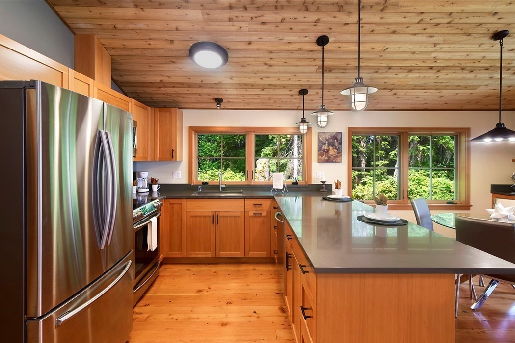 Kitsap Lodge in the woods kitchen with lots of light and beautiful wood finishes, Kingston, Wa.