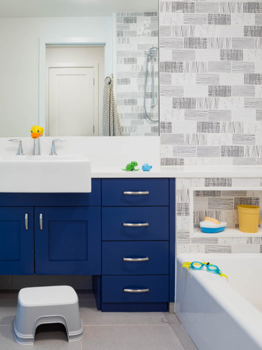 The kids bathroom features simply patterned black and white subway tiles and a pop of color with the blue cabinetry in the Wallingford Urban Farmhouse.
