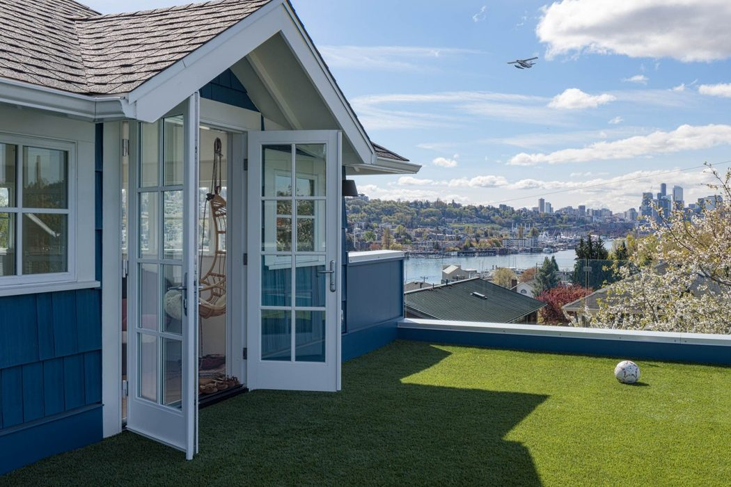 The roof deck with AstroTurf and glass panel railing overlooking lake Union and Seattle on the third story addition of the Urban Farmhouse in Wallingford.