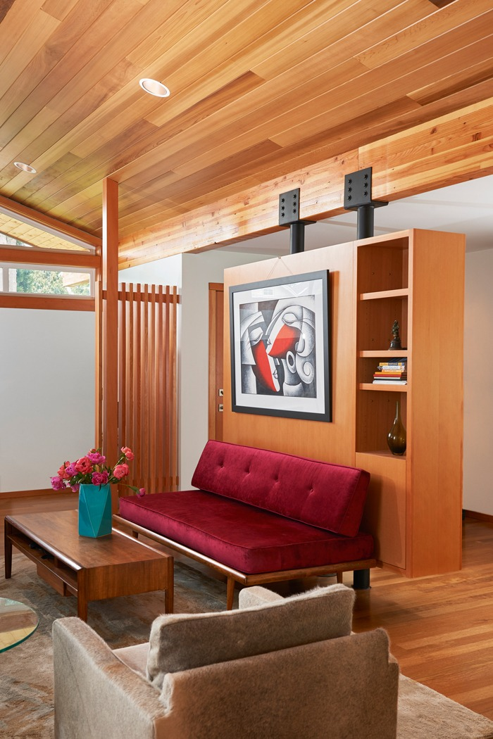 Living room in the Kirkland seattle Mid Century Remodel with exposed beam and wood ceiling, custom interior screen, and floating built in bookshelf wall.