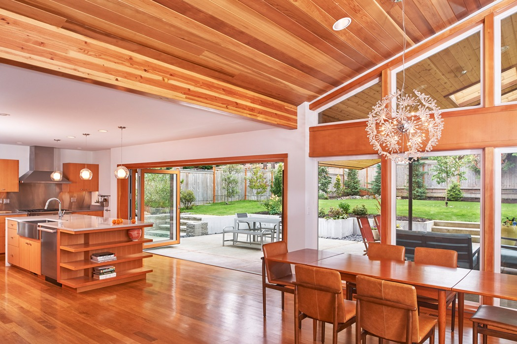 Kirkland seattle Mid Century Modern Remodel open kitchen and dining room, vaulted exposed wood ceiling, custom kitchen island, folding door onto patio.